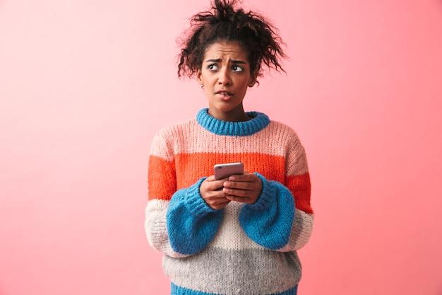 Imagem de uma bela jovem africana triste posando isolada usando telefone celular.