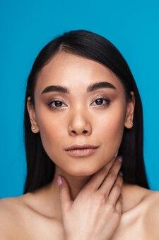 Imagem de uma bela jovem asiática positiva satisfeita posando isolada na parede azul.