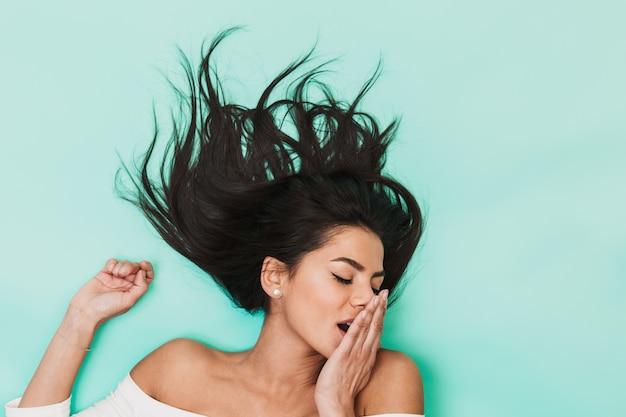 Imagem de uma bela jovem com sono bocejando encontra-se isolada na luz azul. conceito de cabelo saudável.