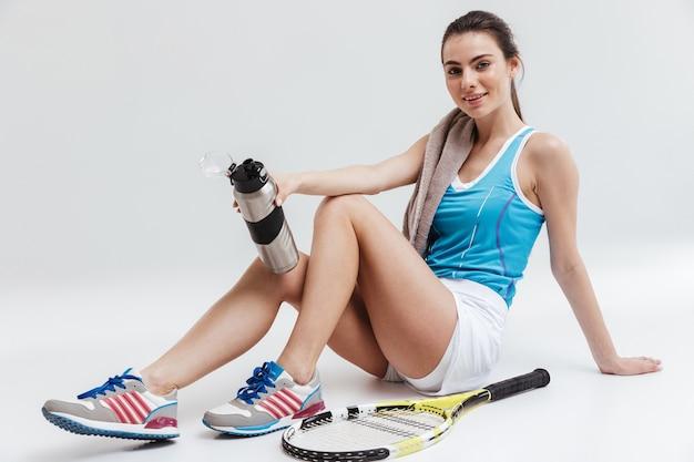 Imagem de uma bela jovem esportista fitness mulher tenista isolada sobre uma parede cinza segurando água.