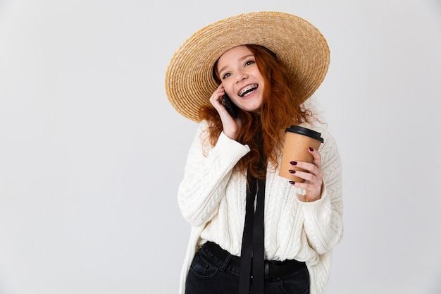 Imagem de uma bela jovem ruiva jovem posando isolado sobre o fundo da parede branca, bebendo café, falando por telefone.