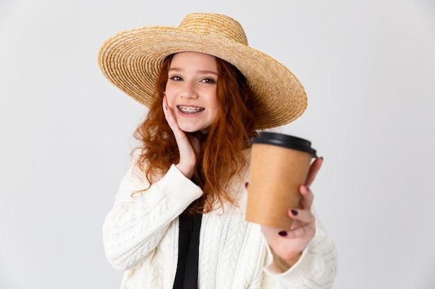 Imagem de uma bela jovem ruiva linda garota posando isolado sobre o fundo da parede branca, bebendo café.