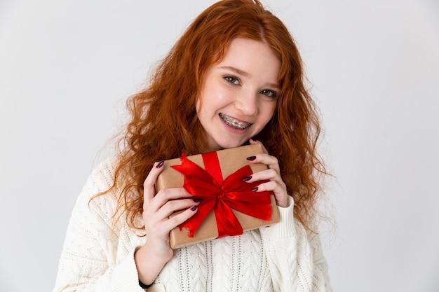 Imagem de uma bela jovem ruiva linda garota posando isolado sobre o fundo da parede branca, segurando a caixa de presente.
