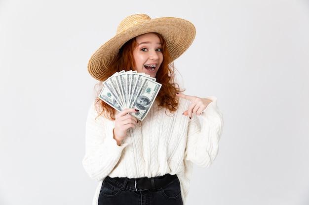 Imagem de uma bela jovem ruiva linda garota posando isolado sobre o fundo da parede branca, usando chapéu segurando dinheiro.