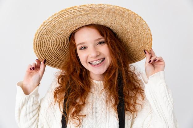 Imagem de uma bela jovem ruiva linda garota posando isolado sobre o fundo da parede branca usando chapéu.