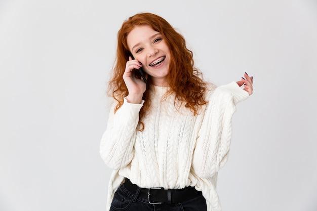 Imagem de uma bela jovem ruiva posando isolado sobre o fundo da parede branca, falando por telefone.