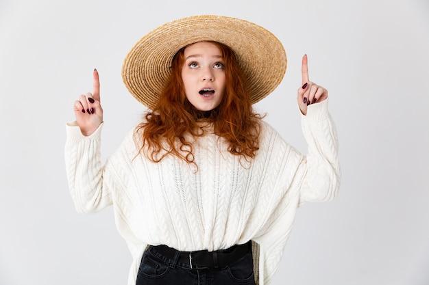 Imagem de uma bela ruiva chocada jovem bonita posando isolado sobre o fundo da parede branca usando chapéu.