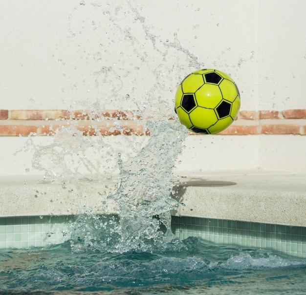 Imagem de uma bola de plástico amarela e preta saltando da água em alta velocidade com respingos de água em alta velocidade