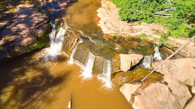 Imagem de uma cachoeira sobre uma rocha com rochas musgosas marrons e água marrom