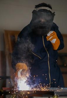 Imagem de uma chapa de aço soldada em uma fábrica industrial. ele usa equipamentos de proteção completos, como máscaras, luvas, roupas de soldagem. esse tipo de trabalho requer habilidades específicas.