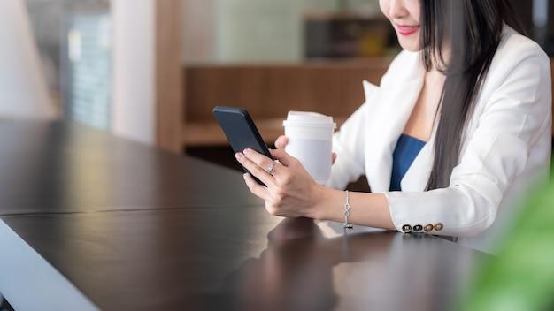 Imagem de uma empresária sorridente e feliz, bebendo café, olhando para um smartphone em um café.