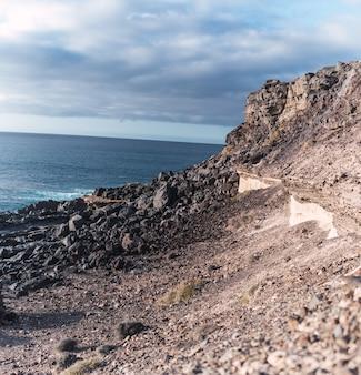 Imagem de uma encosta rochosa ao longo de uma costa marítima sob céu nublado