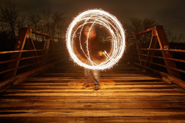 Imagem de uma esfera de luz branca difusa em uma ponte de metal à noite