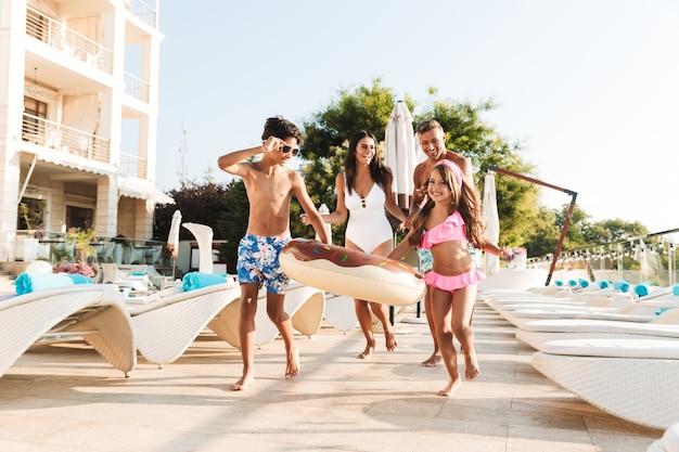 Imagem de uma família caucasiana feliz com crianças descansando perto de uma piscina luxuosa, com espreguiçadeiras e guarda-sóis brancos na frente do hotel