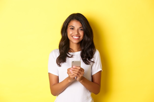 Imagem de uma garota afro-americana moderna sorrindo usando um telefone celular em pé sobre um fundo amarelo