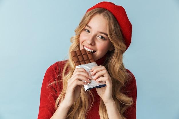 Imagem de uma garota alegre de 20 anos usando uma boina vermelha comendo uma barra de chocolate isolada