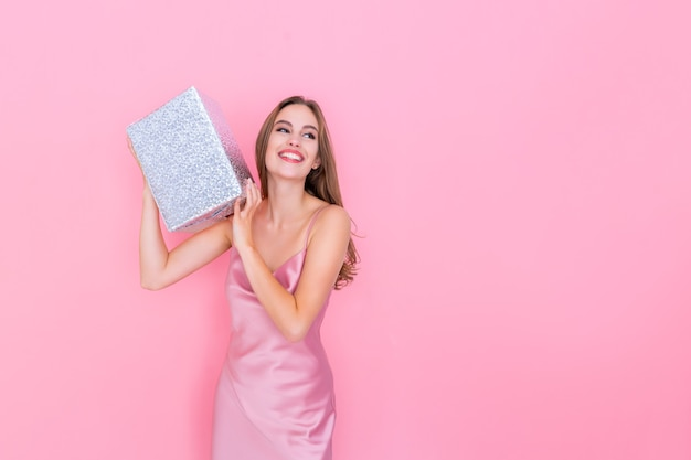 Imagem de uma garota feliz sacudindo a caixa com um presente perguntando o que dentro da caixa embrulhada fica no fundo rosa