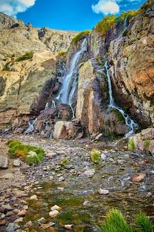 Imagem de uma grande cachoeira em um riacho nas montanhas com pedras cobertas de musgo