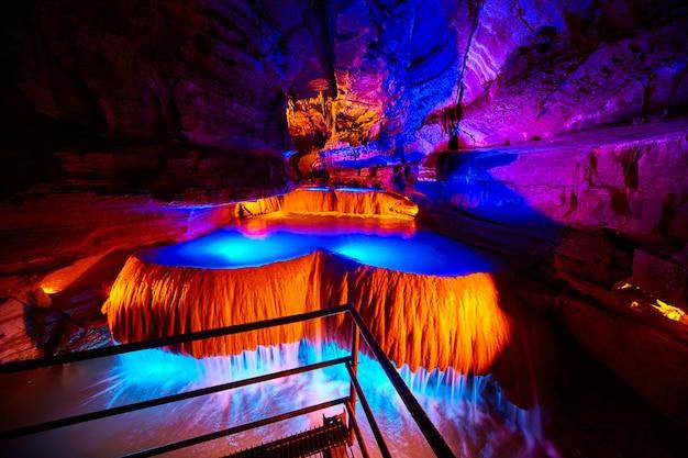 Imagem de uma grande cachoeira subterrânea em uma caverna em um caminho turístico com luzes laranja e azuis