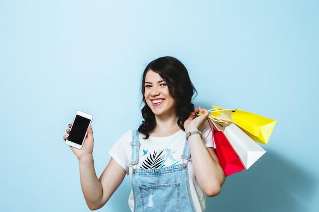 Imagem de uma jovem alegre, mostrando o telefone móvel de tela em branco enquanto carregava isolado sobre sacolas de parede amarela