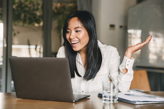Imagem de uma jovem asiática de 20 anos vestindo uma camisa branca, sorrindo e gesticulando com a mão de lado, enquanto fala ou bate-papo por vídeo chamada no laptop no escritório