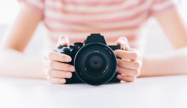 Imagem de uma jovem asiática segurando uma câmera