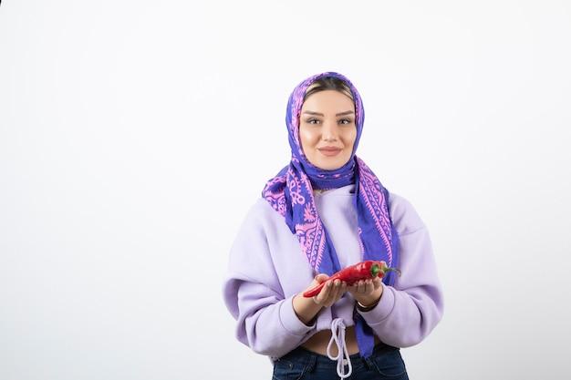 Imagem de uma jovem com um lenço segurando uma pimenta vermelha.