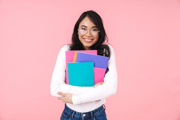 Imagem de uma jovem estudante morena asiática usando óculos e segurando pastas de papel isoladas em rosa