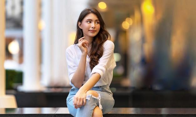 Imagem de uma jovem feliz sentada no chão à noite na cidade
