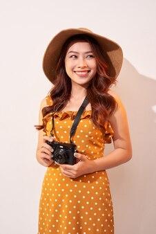 Imagem de uma jovem fotógrafa isolada sobre uma parede bege segurando a câmera.