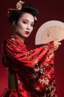 Imagem de uma jovem gueixa em quimono japonês tradicional segurando um leque de mão de madeira