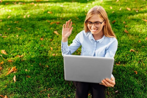 Imagem de uma jovem incrível, sentada num parque, usando um laptop, senta-se em um gramado verde.