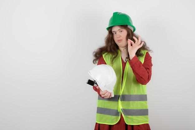 Imagem de uma jovem linda com síndrome de down em pé no colete, mostrando um gesto de ok.