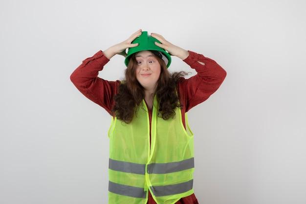 Imagem de uma jovem linda de pé no colete e usando um capacete.