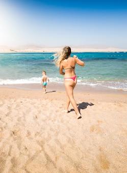 Imagem de uma jovem mãe correndo para seu filho pequeno caminhando no mar. pai atencioso, evitando situações de perigo durante as férias na praia.
