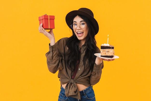 Imagem de uma jovem morena asiática usando um chapéu segurando um bolo de aniversário e uma caixa de presente isolada em amarelo