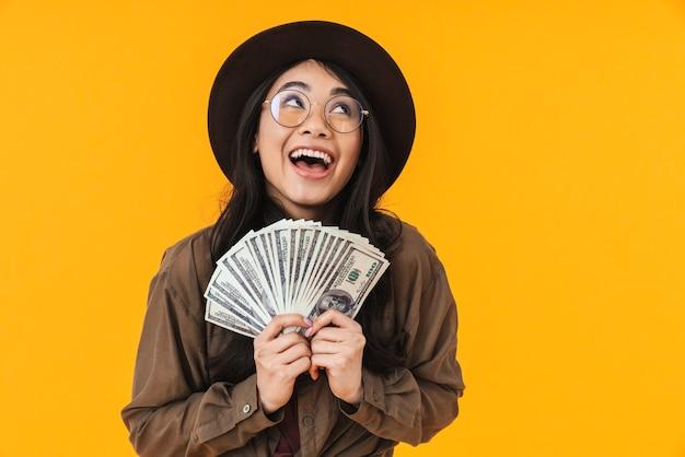 Imagem de uma jovem morena asiática usando um chapéu, sorrindo e segurando um monte de dinheiro isolado no amarelo