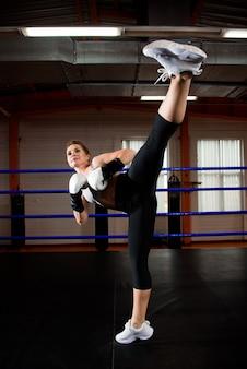 Imagem de uma jovem mulher atlética em luvas de boxe.