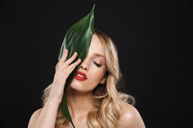 Imagem de uma jovem mulher bonita com lábios vermelhos de maquiagem brilhante posando isolado com flor de folha verde.