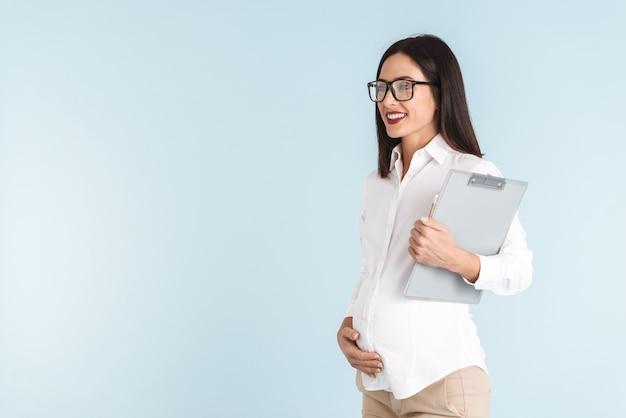 Imagem de uma jovem mulher de negócios grávida isolada segurando a prancheta.