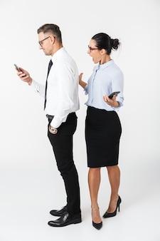 Imagem de uma jovem mulher gritando, olhando para seu colega de negócios, usando telefone celular isolado sobre uma parede branca.