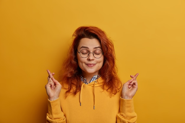 Imagem de uma jovem ruiva esperançosa de aparência agradável mantém os dedos cruzados, deseja boa sorte antes de passar no exame ou ir para uma entrevista de emprego, fecha os olhos