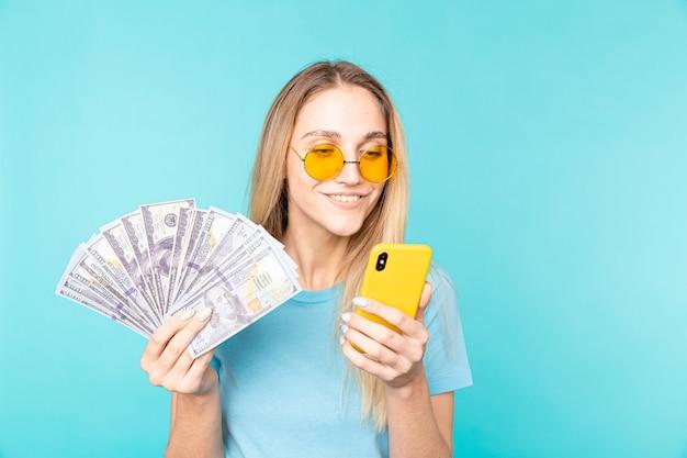 Imagem de uma jovem sorridente segurando o celular e as notas de dinheiro isoladas sobre o azul.