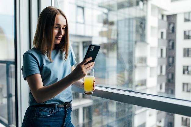 Imagem de uma jovem sorridente usando o celular e bebendo suco em pé perto de uma janela dentro de casa