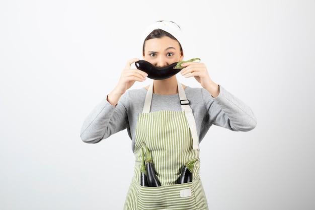 Imagem de uma linda dona de casa com berinjelas no avental e mostrando uma