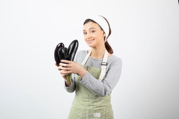 Imagem de uma linda dona de casa feliz com avental segurando berinjelas frescas