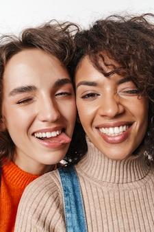Imagem de uma linda feliz alegre otimista duas amigas multirraciais em macacões jeans