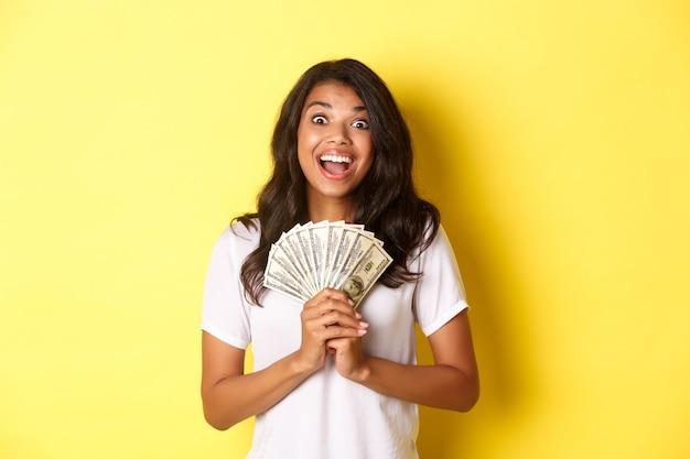 Imagem de uma linda garota afro-americana animada ganhando um prêmio em dinheiro e sorrindo segurando dinheiro