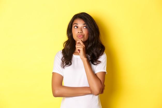 Imagem de uma linda garota afro-americana pensativa fazendo sua escolha, olhando para o canto superior direito