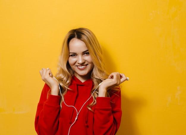 Imagem de uma linda garota animada loira ouvindo música em fones de ouvido e dançando na parede amarela